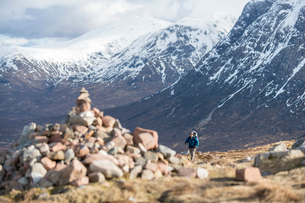 A cairn and a walker at the top of the Devils Staircase while hiking along the West Highland Way neaの写真素材 [FYI03790303]