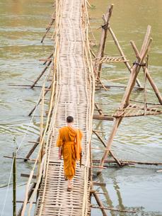 Orange-clad Buddhist monk crossing a bamboo bridge, Luang Prabang, Laos, Indochina, Southeast Asia,の写真素材 [FYI03790485]