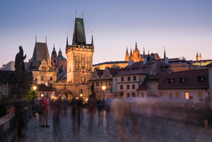 Charles Bridge, Lesser Towers, and Prague Castle at night with blurred pedestrians, UNESCO World Herの写真素材 [FYI03790666]
