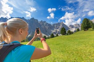Girl takes a photo with a smartphone, Longiaru, Badia Valley, South Tyrol, Dolomites, Italy, Europeの写真素材 [FYI03791207]