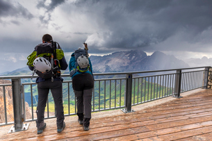 Two mountain climbers watch the storm above Marmolada, Pordoi Pass, Fassa Valley, Trentino, Dolomiteの写真素材 [FYI03791214]