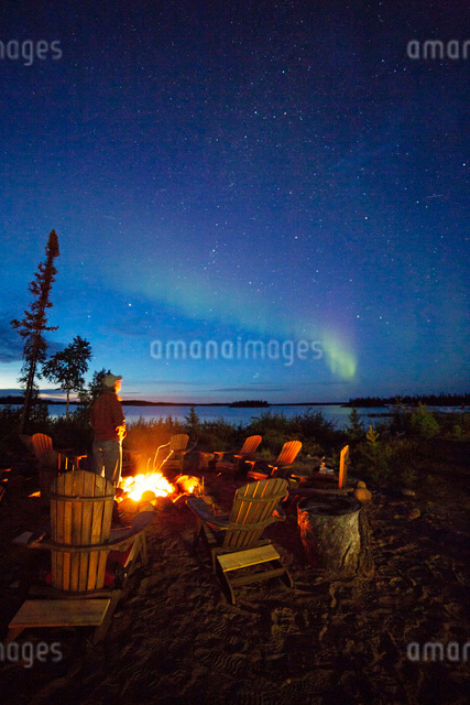 A man views the Northern Lights (aurora borealis) by a camp fire by Lake Egenolf in northern Manitobの写真素材 [FYI03791917]