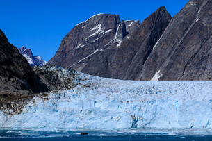 Cruise passengers in zodiac give scale to huge face, Thryms Glacier, Skjoldungen Fjord, glorious weaの写真素材 [FYI03791927]