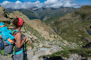 A hiker looks out at the Pyrenees mountains from the top of Col Peyreget while hiking the GR10 trekkの写真素材 [FYI03791962]