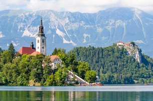 Tiny island with a church, a castle on a crag, and mountain views, Lake Bled, Slovenia, Europeの写真素材 [FYI03792196]