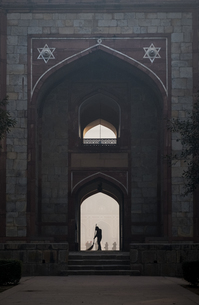 Silhouette of man sweeping under arch of Humayun's Tomb in Delhi, India, Asiaの写真素材 [FYI03793044]