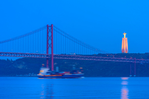 Container ship passing under the Bridge of 25 April and Almada Cristo Rei statue at sunset, Belem diの写真素材 [FYI03793158]