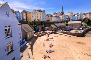 Colourful historic town, St. Mary's church, from Harbour Beach, sunbathers on a sunny day, Tenby, Peの写真素材 [FYI03793451]