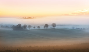 Layers of thick fog wafting across the rolling hills of Kraichgau region shortly after suNoise, Badeの写真素材 [FYI03793547]