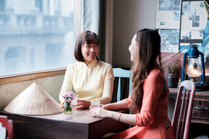 Two friends in Ao Dai dresses taking coffee in a Saigon coffee house, Ho Chi Minh City, Vietnam, Indの写真素材 [FYI03793586]