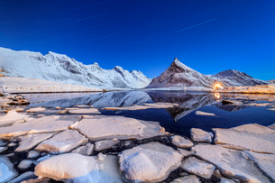 Star trails and lights on the snowy peaks reflected in the cold sea, Volanstinden, Fredvang, Lofotenの写真素材 [FYI03793620]