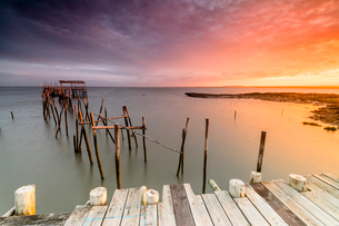 Fiery sky at dawn on the Palafito Pier in the Carrasqueira Natural Reserve of Sado River, Alcacer doの写真素材 [FYI03793636]