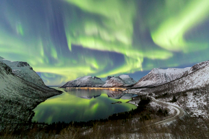 Northern lights (aurora borealis) and stars light up the snowy peaks reflected in the cold sea, Bergの写真素材 [FYI03793645]