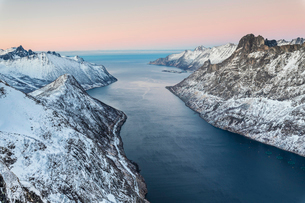 Top view of the snowy peaks surrounding Fjordgard framed by the frozen sea at sunset, Ornfjorden, Seの写真素材 [FYI03793648]