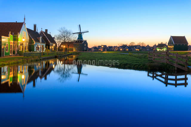 Blue lights at dusk on wooden houses and windmills of the typical village of Zaanse Schans, North Hoの写真素材 [FYI03793654]