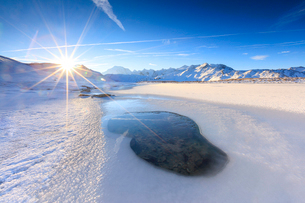 Rays of sun on the frozen Lake, Piz Umbrail framed by Mount Ortles in background, Braulio Valley, Vaの写真素材 [FYI03793655]