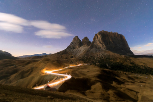 Lights of car trails with Sassopiatto in the background, Dolomites, South Tyrol, Italy, Europeの写真素材 [FYI03793663]