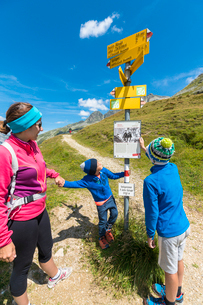 Mother and sons look at the signpost of hiking trails, Spluga Pass, Chiavenna Valley, Spluga Valley,の写真素材 [FYI03793689]