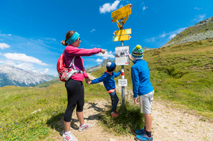 Mother and sons look at the signpost of hiking trails, Spluga Pass, Chiavenna Valley, Spluga Valley,の写真素材 [FYI03793692]