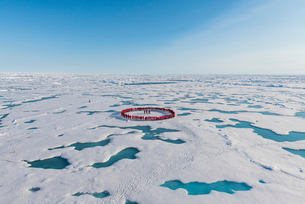 People wearing red forming circle around North Pole, Arcticの写真素材 [FYI03793862]