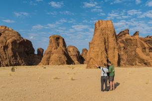 Couple looking at beautiful rock formations, Ennedi Plateau, UNESCO World Heritage Site, Ennedi regiの写真素材 [FYI03793912]