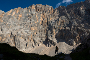 A trekker takes a break from the trail under the impressive northwest vertical wall of Monte Civettaの写真素材 [FYI03795787]