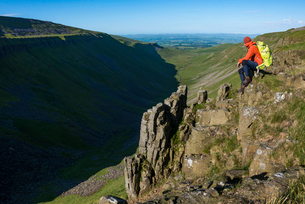 A man hiking the Pennine Way sits on the edge of the huge escarpment called Highcup Nick in the Yorkの写真素材 [FYI03795797]