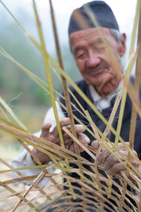 A old Nepali man makes a traditional basket by weaving bamboo, Kathmandu Valley, Nepal, Asiaの写真素材 [FYI03795803]