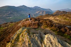 A woman trekking in Snowdonia walks across the top of Mynydd Sygun near Bedgellert with views of Mouの写真素材 [FYI03795805]
