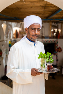An Egyptian man holds a tray with a glass of mint tea and some fresh mint leaves, Aswan, Egypt, Nortの写真素材 [FYI03795823]