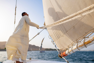 An Egyptian man stands on the bow of a traditional Felucca sailboat with wooden masts and cotton saiの写真素材 [FYI03795826]