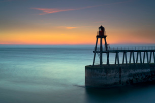 Daybreak over Whitby East Pier and lighthouse, North Yorkshire, England, United Kingdom, Europeの写真素材 [FYI03795907]