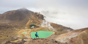 Man taking photos of Emerald Lakes, Tongariro Alpine Crossing, Tongariro National Park, UNESCO Worldの写真素材 [FYI03796511]