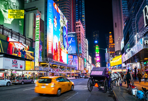 The bright lights of New York City's Times Square with an iconic yellow cab passing through, New Yorの写真素材 [FYI03796575]