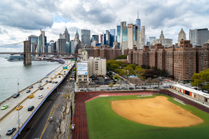 A baseball field along the FDR and East River with views towards the Brooklyn Bridge and Lower Manhaの写真素材 [FYI03796580]