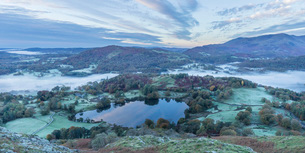 View of Loughrigg Tarn and early morning mists in autumn from Loughrigg Fell, Lake District Nationalの写真素材 [FYI03796665]