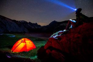 A person looks at stars near his red tent, Unterer Segnesboden, Flims, District of Imboden, Canton oの写真素材 [FYI03796775]