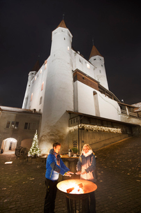 A couple of people warm their hands with the castle in the background, Thun, Canton of Bern, Switzerの写真素材 [FYI03796827]