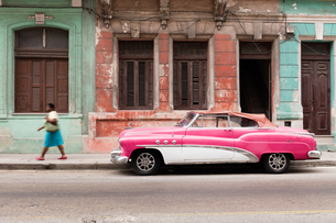 Woman walks past a pink and white vintage car, parked on street in Havana, Cuba, West Indies, Caribbの写真素材 [FYI03797114]