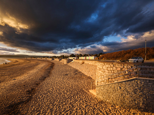 Under dramatic clouds, strong warm sunlight illuminates the beach and sea defences on the sea frontの写真素材 [FYI03797197]