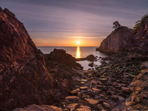 A colourful sunrise over Torbay with warm light on rocks, Babbacombe, Torquay, Devon, England, Uniteの写真素材 [FYI03797274]