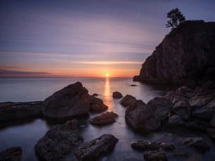 A colourful sunrise over Torbay with warm light on rocks, Babbacombe, Torquay, Devon, England, Uniteの写真素材 [FYI03797275]