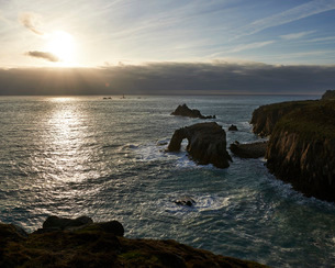Sunset at Land's End over Enys Dodman rock arch, Longships Lighthouse, Cornwall, England, United Kinの写真素材 [FYI03797302]