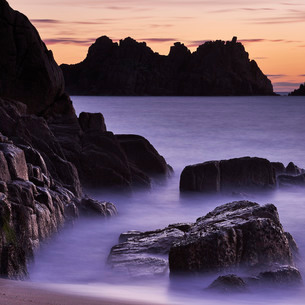 Early morning on the beach looking out towards Logan Rock at Porthcurno, Cornwall, England, United Kの写真素材 [FYI03797303]