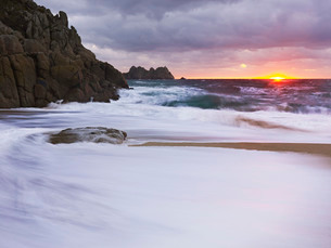 Early morning on the beach looking out towards Logan Rock at Porthcurno, Cornwall, England, United Kの写真素材 [FYI03797306]