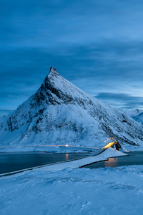 Fredvang Bridge set against pyramid shaped mountain at night with light trails, Lofoten, Arctic, Norの写真素材 [FYI03797842]