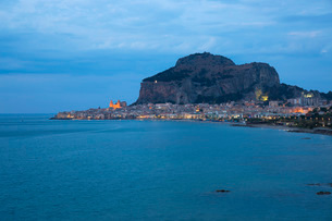 View along coast to the town and illuminated cathedral, dusk, La Rocca towering above, Cefalu, Palerの写真素材 [FYI03797950]