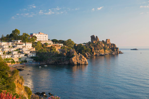 View across the tranquil waters of Calura Bay, sunrise, ancient watchtower visible on headland, Cefaの写真素材 [FYI03797956]