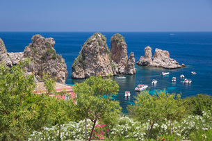 View from hillside over tranquil cove to the Faraglioni, a series of offshore rock stacks, Scopello,の写真素材 [FYI03797983]