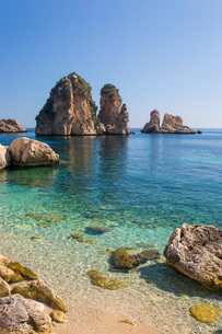 View across tranquil cove to the Faraglioni, a series of towering offshore rock stacks, Scopello, Trの写真素材 [FYI03797986]